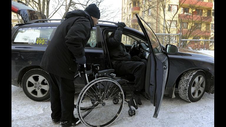 Färdtjänstkund med rullstol sätter sig i färdtjänsttaxi.