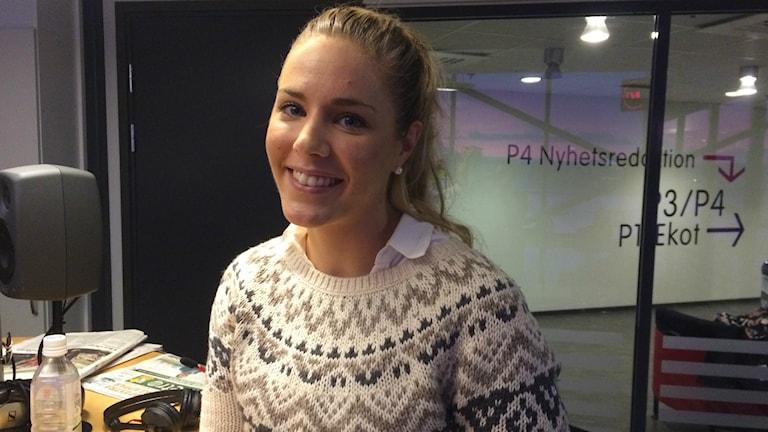 Vit kvinna med mellanblont hår i en stickad vit och beige tröja. Sitter i studio och ler in mot kameran. Foto: Lovisa Fischerström/SR.
