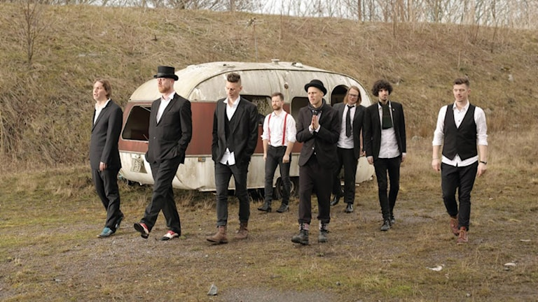 Åtta vita män i kostymer går utomhus med en husvagn i bakgrunden. Foto: Hendrik Zeitler.