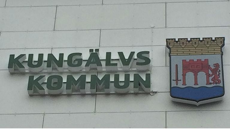 Bild på Kungälvs skylt på stadshuset, med kommunvapnet.