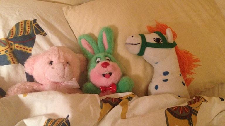 Tre gossedjur ligger i en säng.