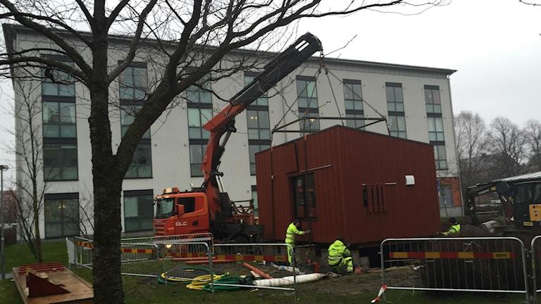 SGS röda kvadratiska passivhus sänks ner framför ett studentboende i Kviberg. Foto: Monir Louidyi/Sveriges Radio