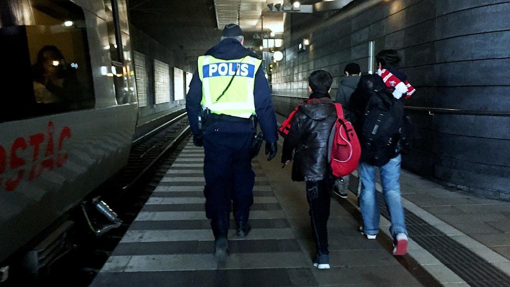 Polis med två bagagetyngda småpojkar - ensamkommande.