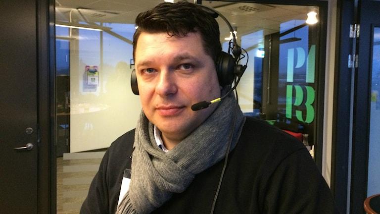 Ljushyad man med mörkt kort hår, har headset på huvudet, en grå halsduk runt halsen och en svart tröja. Tittar in i kameran. Foto: Peo Wenander/SR.