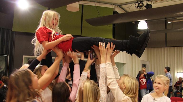 En flicka blir hissad av sina klasskamrater efter seger i kvartsfinal Vi i femman. Foto: Madeleine Blidberg/SR