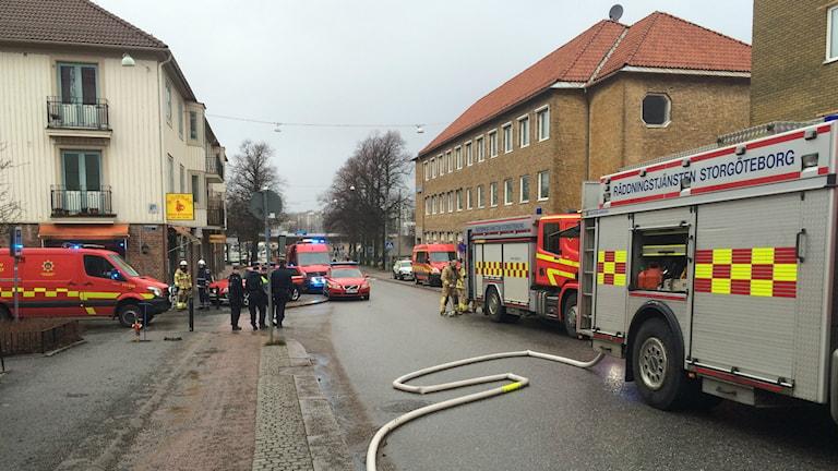 Flera brandbilar står på en gata och flera brandmän arbetar med slangarna. Foto: Simon Rissvik/SR