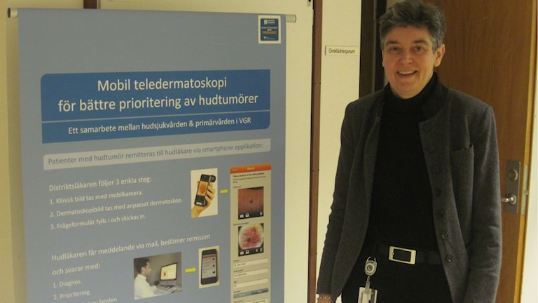 Verksamhetschefen på hudmottagningen, Helena Gustafsson, framför affisch om det som kan bli framtiden: bedömning av hudbilder på håll teledermatoskopi. Foto: Epp Anderson/Sveriges Radio