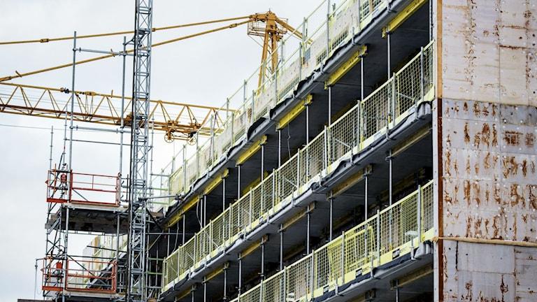 Här växer ett nytt flerfamiljshus fram. Flera våningar med byggställningar.
