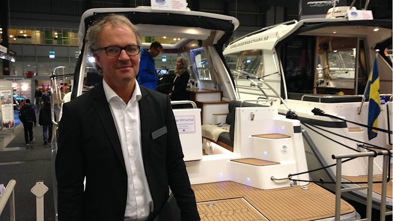 Håkan Carlander står framför en stor motorbåt.