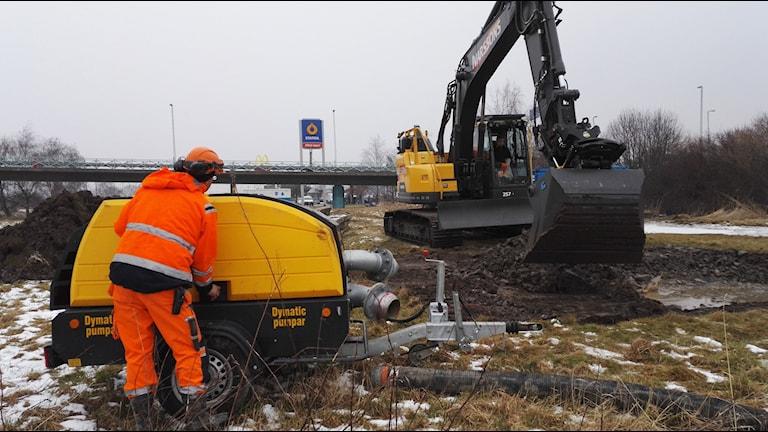 En grävmaskin och en arbetare jobbar med att få stopp på en vattenläcka längs en bilväg.