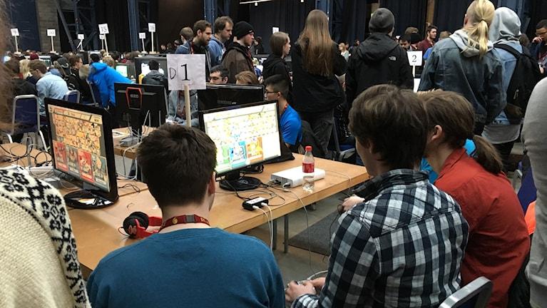 Tre personer tittar på en datorskärm.