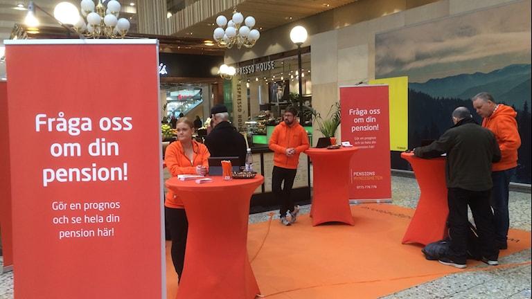 Pensionsmyndighetens informatörer klädda i orange  svarar på allmänhetens frågor i Nordstan om pensionen