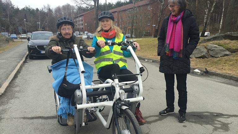 En pensionär och en yngre kvinna cyklar bredvid varandra på en cykel med tre hjul på en asfalterad gata. En kvinna står och tittar på.