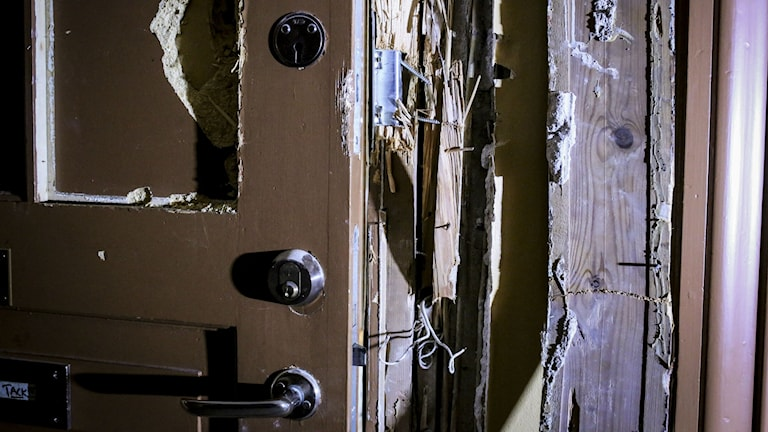Närbild på uppbruten dörr . Bara flisor kvar av del av dörr.