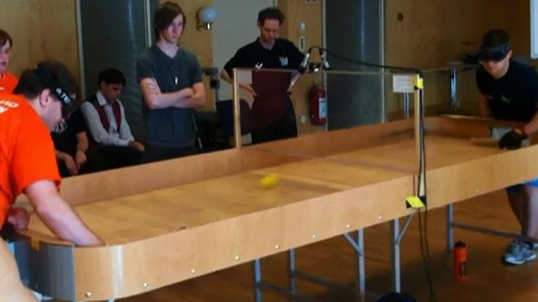 Spelare spelar showdown - pingis för blinda på träbord med höga sarger och ett nät man ska skjuta under.