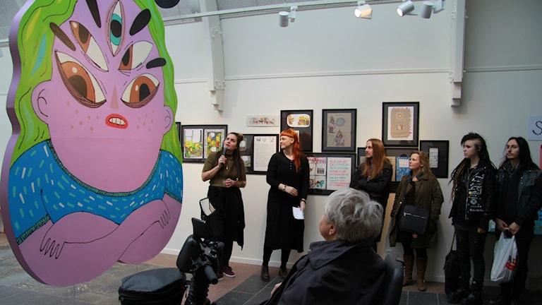 """Konstnären Lisa Ewald med mikrofon berättar om sitt verk """" Det regna """" på utställningen Serieupproret"""