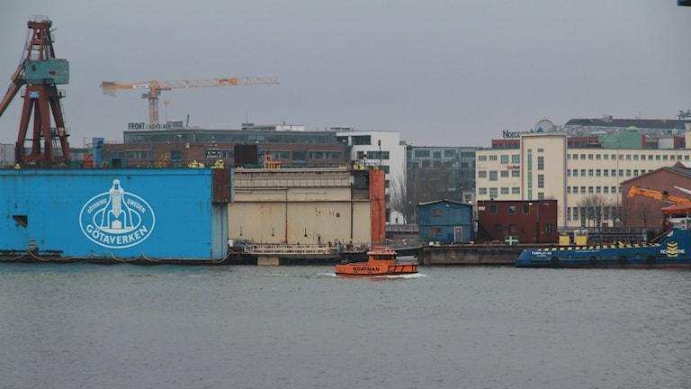 En liten orange lotsbåt väntar på att kunna bogsera bort Götaverkets gamla blå flytdocka.