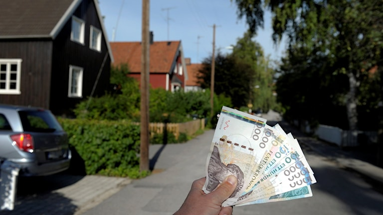bild på hus och en hand som håller pengar