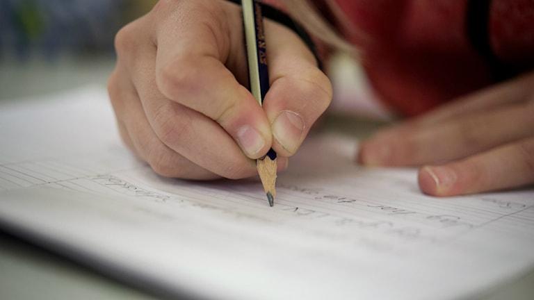 En elev skriver i ett skrivblock.