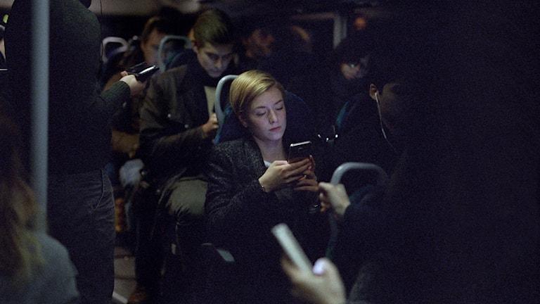 Clara Henry sitter och tittar i telefon på tåg