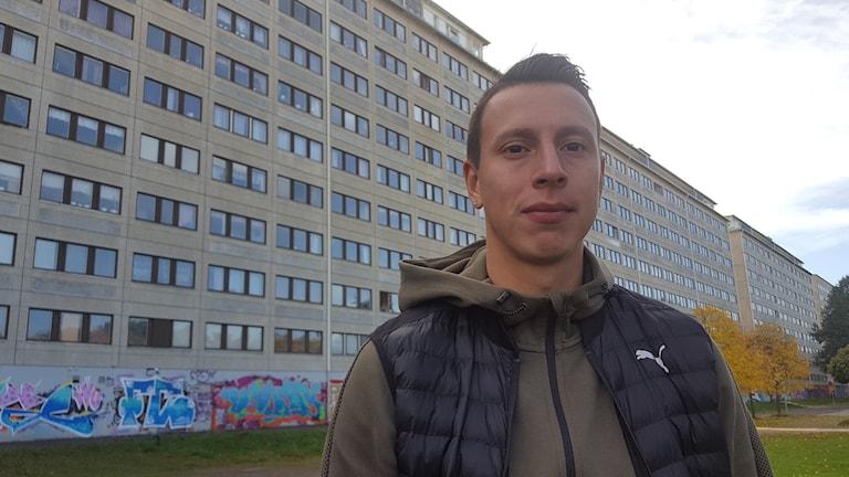 Martin Smedberg Dalence framför hyreshus i Hammarkullen.