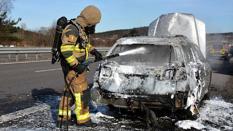Räddningstjänsten släcker bilbranden.