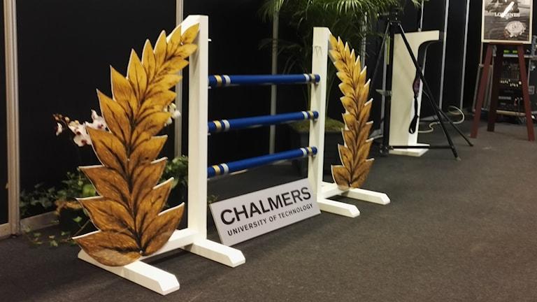 Ett hästhoppningshinder med blåa ribbor. På en skylt står det Chalmers.
