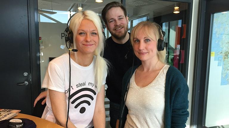 Tre vita personer i studion. Till vänster kvinna med långt blont hår. I mitten en man med brunt hår och skägg och till höger en kortare kvinna med blont hår uppsatt i tofs och lugg.