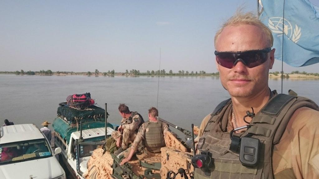 FN-soldaten Oscar Karlflo framför bilar, militärfordon och soldater