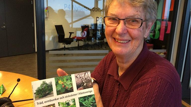 """Evastina Blomgren visar upp boken """"Träd, ormbunkar och stråväxter i Västsverige"""""""
