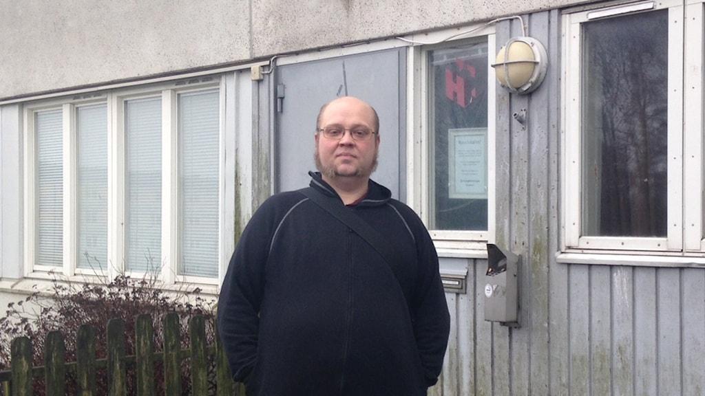 Man som står framför en husvägg