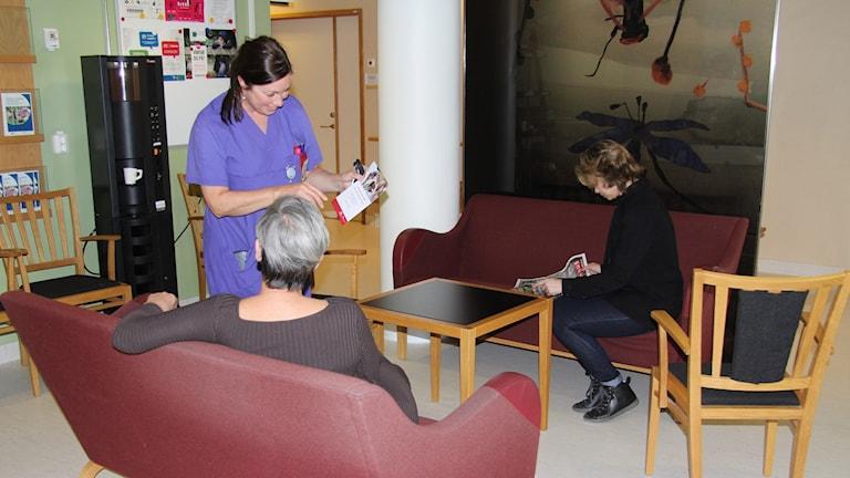 En sjuksköterska pratar med en patient i ett väntrum
