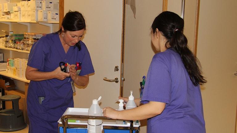 Två sjuksköterskor runt en vagn med vårdutrustning