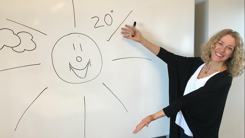 Ylva Nilsson framför en tavla där en sol är ritad