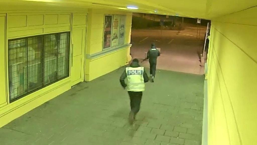 Två personer , en med en polisväst, från en övervakningskamera.