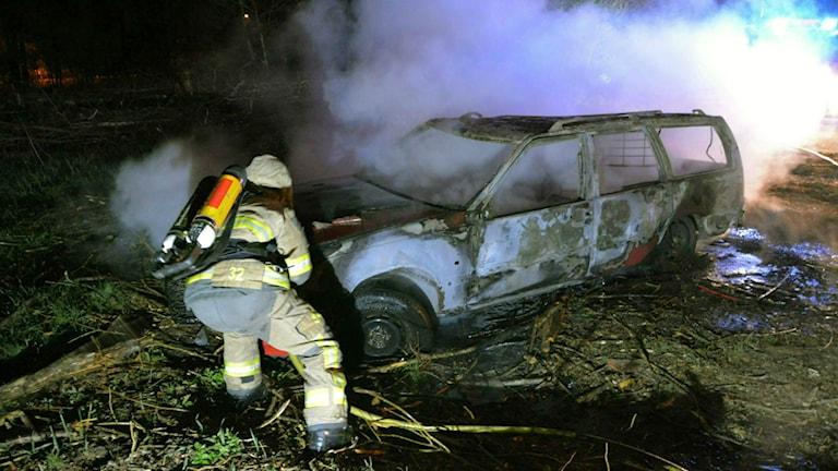 Brandman har just släckt en totalt övertänd bil.