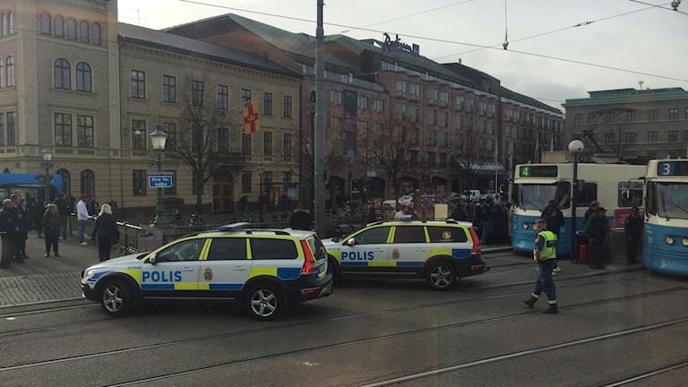 Två polisbilar framför spårvagnar.