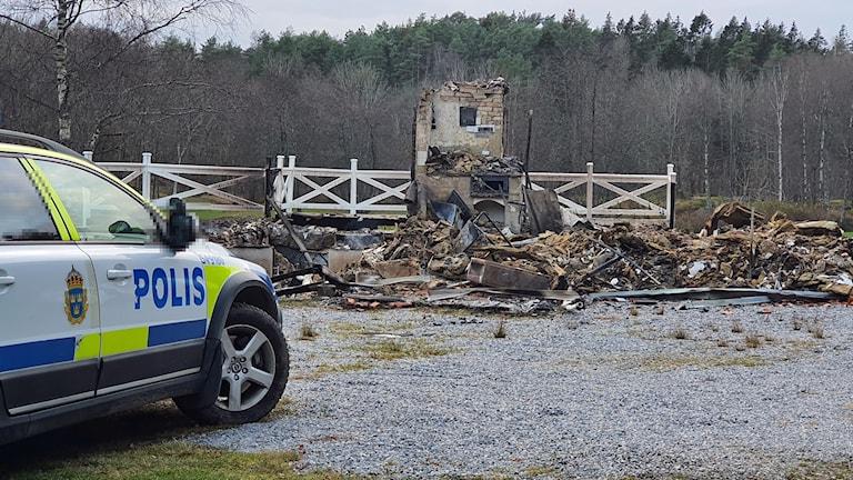 En ruin återstår av den byggnad som brunnit ner. Intill står en polisbil parkerad.
