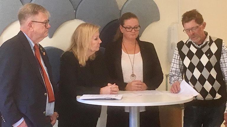 Två män och två kvinnor står vid ett bord