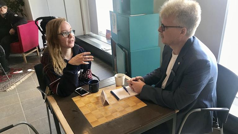 En yngre tjej och en man sitter vid ett bord och diskuterar