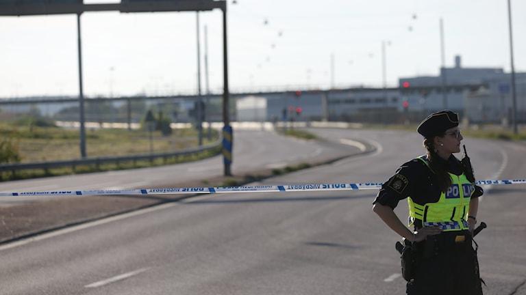 Polisman vid avspärrad väg.
