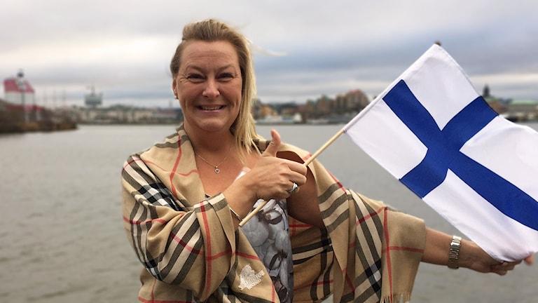 Foto av Eija Kreivi med en finsk flagga i handen.