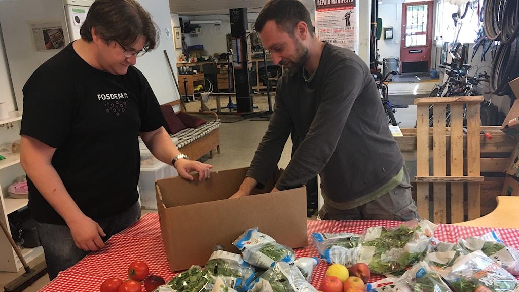 Nicolas Sahlqvist och Tomasz Cieslak plockar upp mat på ett bord.