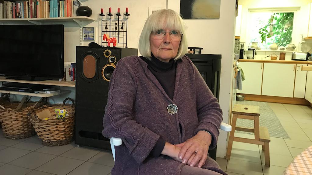 Kvinna med page och glasögon sitter i stol med sitt hem i bakgrunden