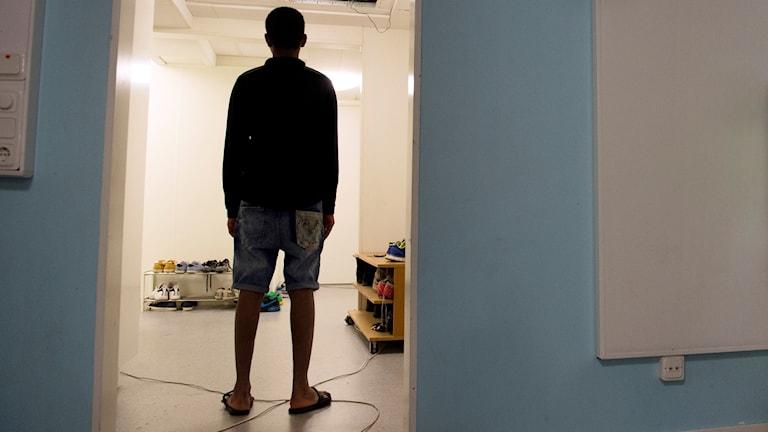 En UNG KILLE  står ensam i en hall. Man ser bara honom som en siluett.