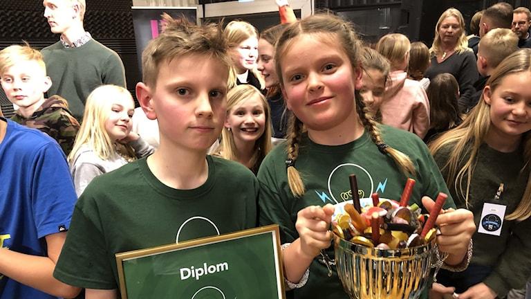 Två barn med en pokal med godis och ett diplom.