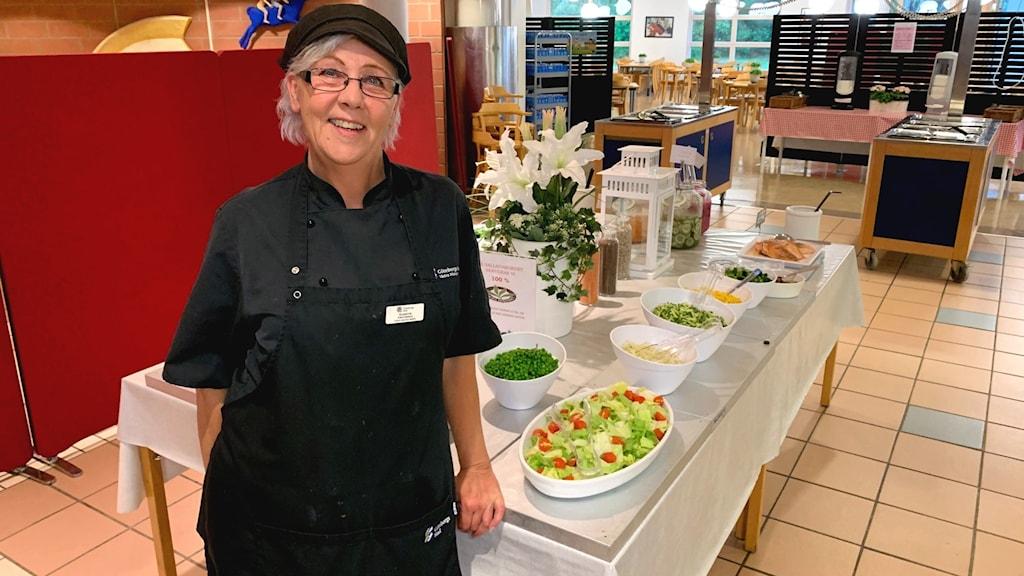En kvinna med glasögon, mörkblått förkläde och keps står leende vid en salladsbuffé.