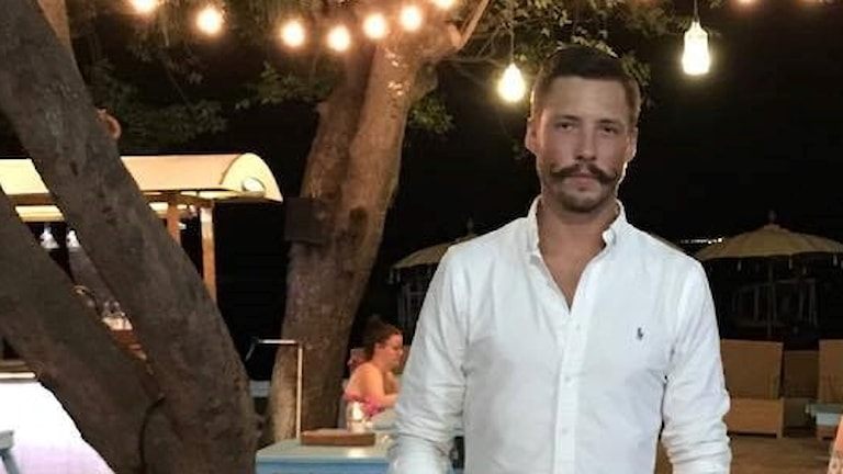 Man med mustasch i tropisk miljö