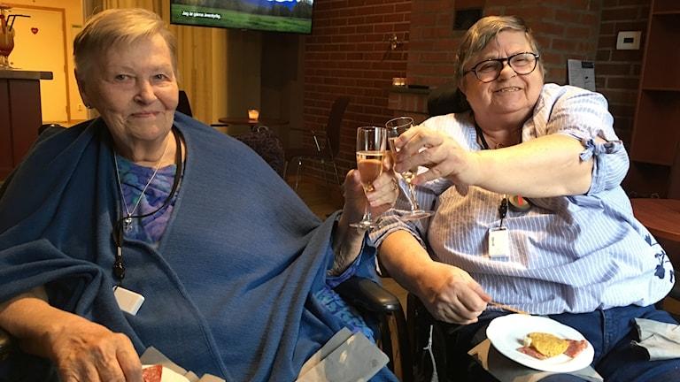 Två rullstolsburna damer skålar i champagne. Barbro Svats och Lisbeth Tamnes