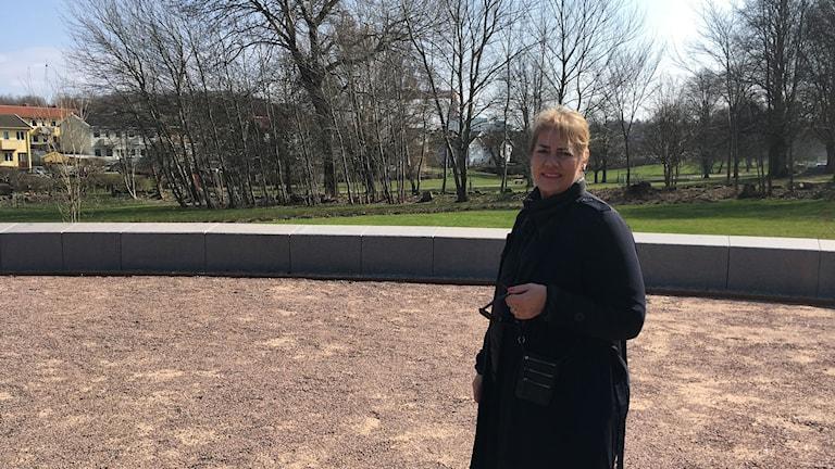 Marie Louise Nord står framför en mur på en grusplan. Bakom den är en gräsmatta och en skogsdunge.